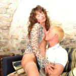 Halbnackte Frau sitzt auf dem Schoss eines blonden Mannes